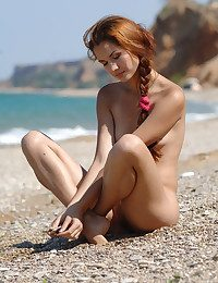 Pretty youthfull woman takes her rosy swim-suit off coupled with poses artistically on the bonny beach.