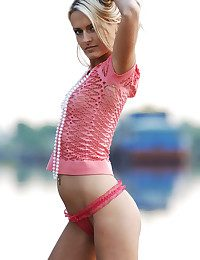 Lovely blondie in the pinkish half-shirt and pinkish undies takes her clothes off and poses on the sea beach.
