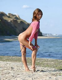 Highly ultra-cute slender dame in morose pinkish cut-offs and top displays her slit on the beach.
