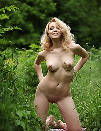 Highly good gold female takes her rosy clothes off and has a rest outdoor on a green grass.