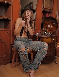 Milena exudes a sultry, foxy, and mysterious honey in fedora hat, tattered jeans, and clouded suspenders.