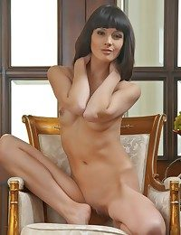Well-composed poses and easy provocative Luiza on tip of an fashionable cushioned chair.